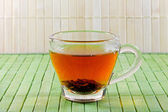 Cup of tea in front of a straw mat — Stock Photo
