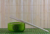 Green teapot and chopsticks against straw mat — 图库照片