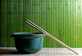 Teapot and chopsticks against a straw mat — 图库照片