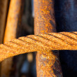 Old rusty iron rope against metal armature — Stock Photo