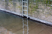 Metal ladder on stone wall at the river — Stock Photo