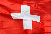 Swiss flag in wind in the sunlight — Stock Photo