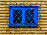 Old barred window in brick wall — Stock Photo
