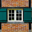 Window with shutters in brick wall of half timbered house — Stock Photo #49494267