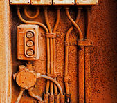 Old electric switch on a rusty iron wall — 图库照片