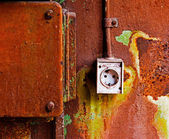 Old electrical outlet on the rusty iron wall — Stock Photo