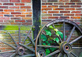 Old ruined cartwheels at wall of farm house — Foto Stock