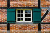 Window with shutters in brick wall of half timbered house — Stock Photo