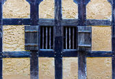 Wooden shutters in the wall of old adobe house — Stock Photo