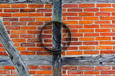 Brick wall of  half timbered house and iron hoop — Stock Photo