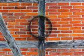 Brick wall of  half timbered house and iron hoop — Stock Photo