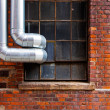 Steel pipes outside the window of brick building — Stock Photo #51046055