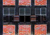 Windows with shutters in brick wall of the half timbered house — Stock Photo