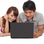 Happy couple using laptop — Stock Photo #17456471