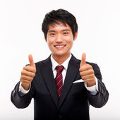 Showing thumb young Asian business man. — Stock Photo
