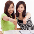 Young Asian student women showing thumb on the desk — Stock Photo #17626367