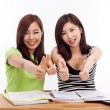 Stock Photo: Young Asian student women showing thumb on the desk