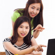Two Asian young woman using computer on the desk — Stock Photo #17626723
