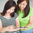 Stock Photo: Two Asian young woman using tablet PC.