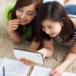 Stock Photo: Two Asian young woman using tablet PC and studying.
