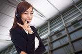 Smiling call center operator asian business woman — Stock Photo
