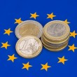 Euro coins on european flag - Stock Photo