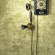 Stock Photo: Antique telephone on a grungy yellow wall
