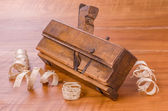 Old molding plane with shavings on a cherry wood board — Stock Photo