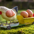 Stock Photo: Antique papier mâché rooster on cart with eggs