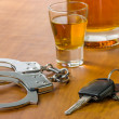 Stock Photo: Shot glass with car keys and handcuffs