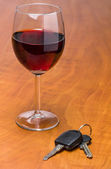 Red wine glass with car keys — Stock Photo