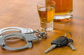 Shot glass with car keys and handcuffs — Stock Photo