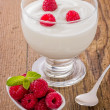 Fresh creamy natural yogurt with raspberries — Stock Photo