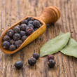 Spice scoop with juniper berries and bay leaves — Stock Photo
