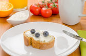 Baguette with cream cheese and blueberries on a breakfast table — Stock Photo