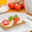 Crispbread with tomato and mozzarella on a breakfast table - Stock Photo