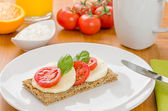 Crispbread with tomato and mozzarella on a breakfast table — Stock Photo