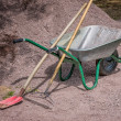 Wheelbarrow with shovel and rake — Stock Photo
