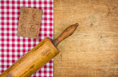 Rolling pin with mold on a wooden board with a checkered tablecloth — Stock Photo