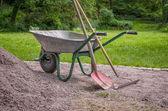 Wheelbarrow with shovel and rake — Stock Photo