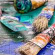 Brush, spatula and color pigments on a wooden palette — Stock Photo