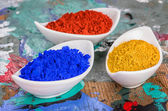 Vibrant color pigments in porcelain bowls on a wooden palette — Stock Photo