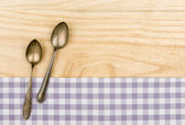 Two silver spoons on a purple checkered table cloth on a wooden background — Stock Photo