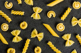 Different types of pasta on a slate background — Stock Photo