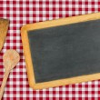 Stock Photo: Empty blackboard with wooden spoons on red checkered table cloth