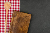 Wooden spoon and cookbook on a slate plate — Stock Photo