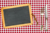 Empty blackboard with silverware on a checkered tablecloth — Stock Photo