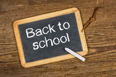 Blackboard with the text Back to school on a wooden table — Stock Photo
