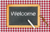 Blackboard with text Welcome on a checkered tablecloth — Stock Photo