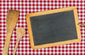 Empty blackboard with wooden spoons on a red checkered table cloth — Stock Photo